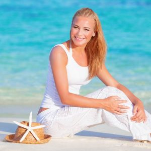 Portrait of cute blond girl sitting on white sandy beach on blue water background, happy summer vacation, travel and tourism concept
