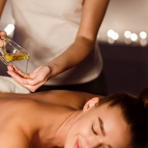 Relaxing treatment. Masseur pouring aroma oil on hand, preparing for massage