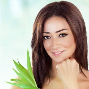 Closeup portrait of beautiful brunette woman with fresh green leaves over blue blur background, healthy lifestyle, enjoying day spa