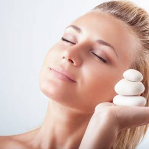 Portrait of gentle calm girl with closed eyes and holding on hand spa stones over light background, natural skin care, peace and zen balance